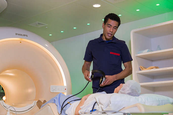 MRI laborant helping patient on exam bed