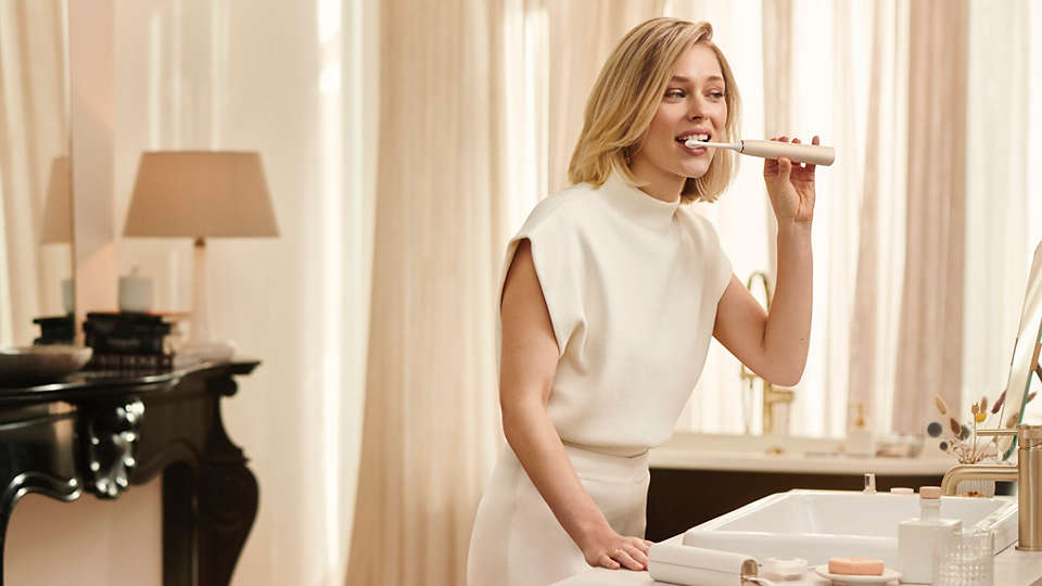 Woman using Sonicare 9900 Prestige